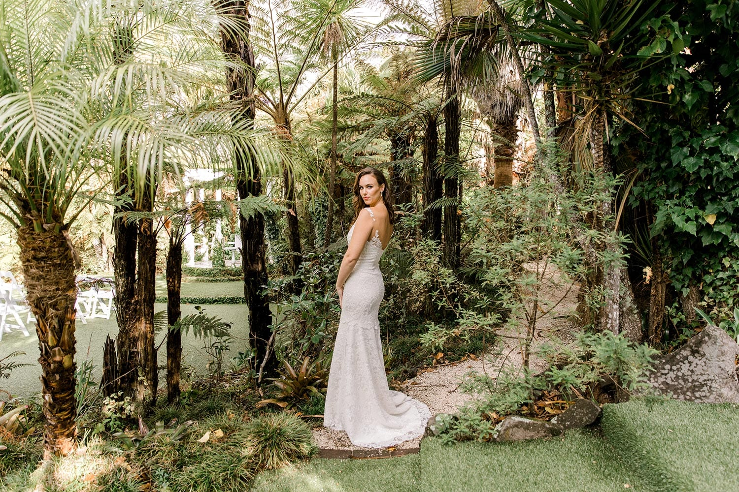 Dakota Wedding Dress from Vinka Design. This full-lace wedding dress is form fitting, sculpting the body beautifully. Delicate beaded lace flowers are hand-appliqued up the sheer nude tulle straps on both the front & back. Full length landscape with model turned away showing detail on back of dress, photographed at Tui Hills by Emmaline Photography.