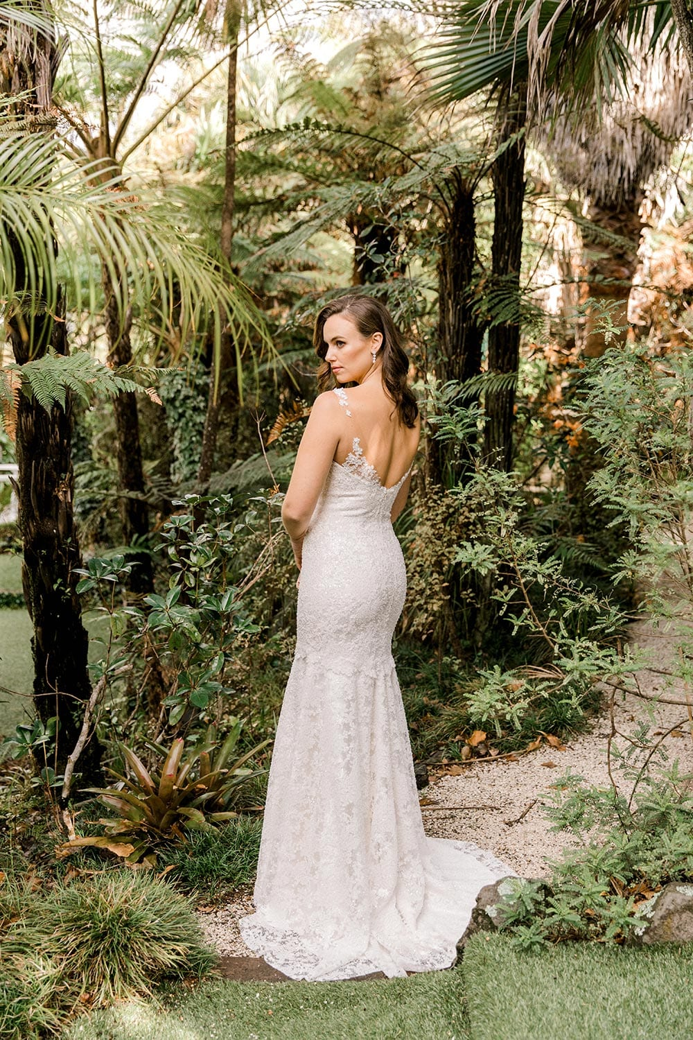 Dakota Wedding Dress from Vinka Design. This full-lace wedding dress is form fitting, sculpting the body beautifully. Delicate beaded lace flowers are hand-appliqued up the sheer nude tulle straps on both the front & back. Full length with model turned away showing detail on back of dress, photographed at Tui Hills by Emmaline Photography.