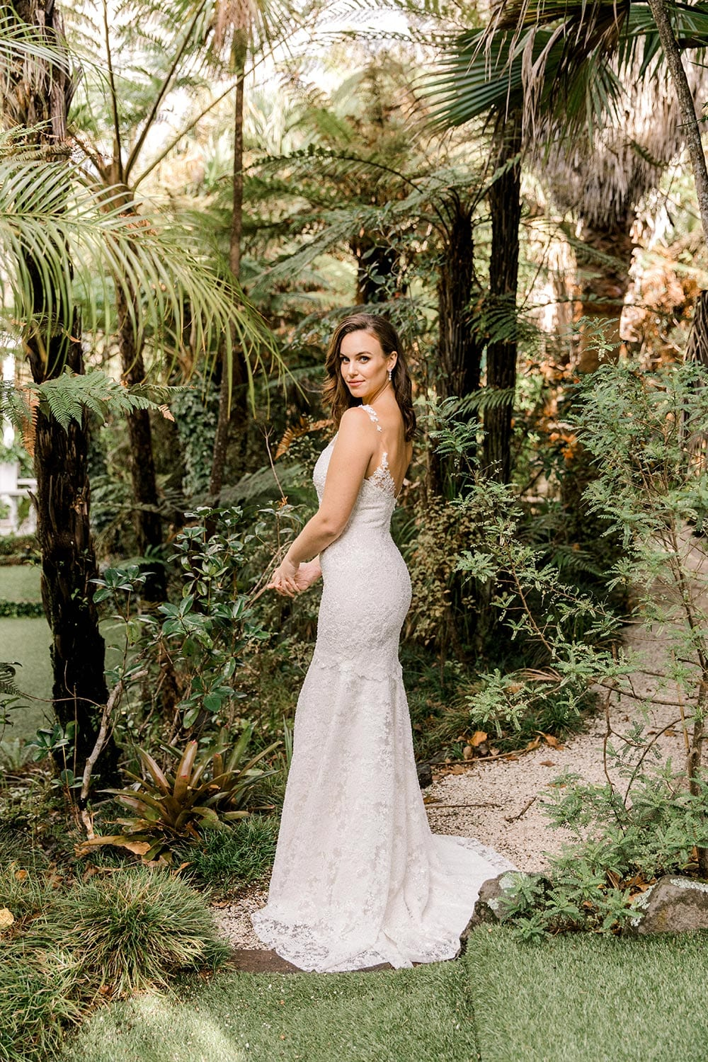 Dakota Wedding Dress from Vinka Design. This full-lace wedding dress is form fitting, sculpting the body beautifully. Delicate beaded lace flowers are hand-appliqued up the sheer nude tulle straps on both the front & back. Full length portrait with model turned away showing detail on back of dress and train, photographed at Tui Hills by Emmaline Photography.