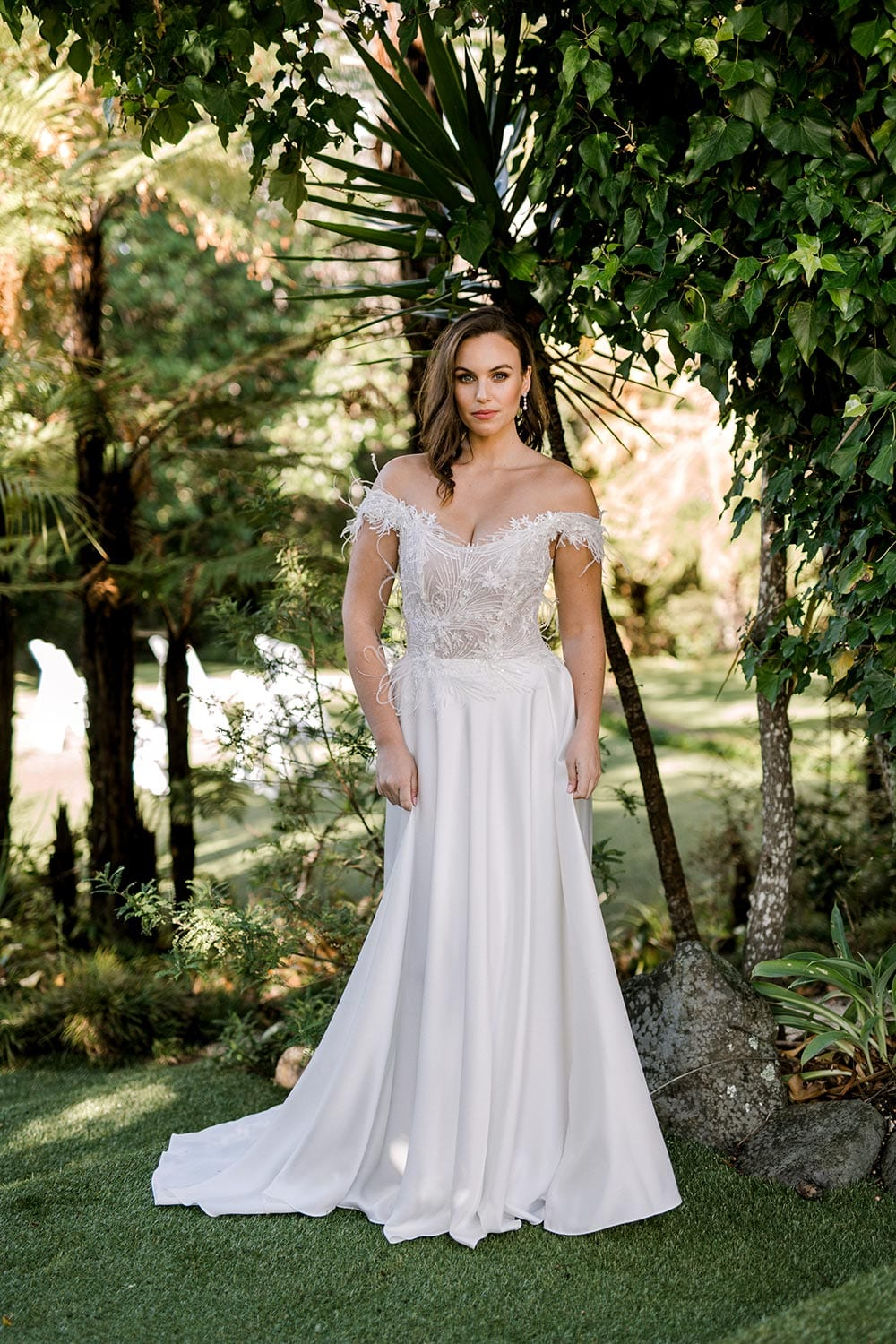 Genevive Wedding Dress from Vinka Design. The soft off-the-shoulder sleeves & semi-sheer structured bodice with hand-appliqued lace and a soft satin skirt make this a romantic & dreamy wedding dress. Full length portrait, photographed at Tui Hills.