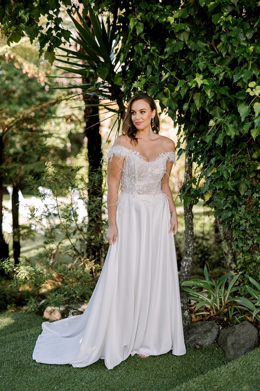 Genevive Wedding Dress from Vinka Design. The soft off-the-shoulder sleeves & semi-sheer structured bodice with hand-appliqued lace and a soft satin skirt make this a romantic & dreamy wedding dress. Full length portrait with train to side, photographed at Tui Hills.