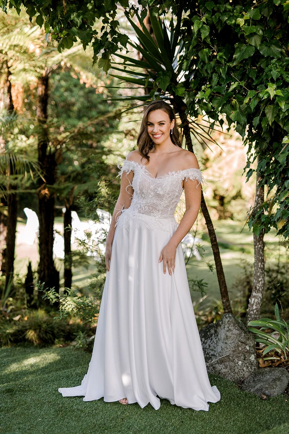 Genevive Wedding Dress from Vinka Design. The soft off-the-shoulder sleeves & semi-sheer structured bodice with hand-appliqued lace and a soft satin skirt make this a romantic & dreamy wedding dress. Full length detail of dress, photographed at Tui Hills.