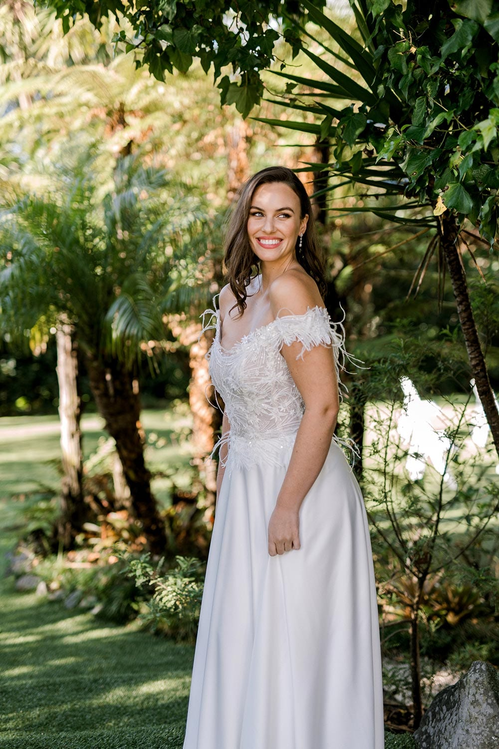 Genevive Wedding Dress from Vinka Design. The soft off-the-shoulder sleeves & semi-sheer structured bodice with hand-appliqued lace and a soft satin skirt make this a romantic & dreamy wedding dress. Side detail of dress, photographed at Tui Hills.