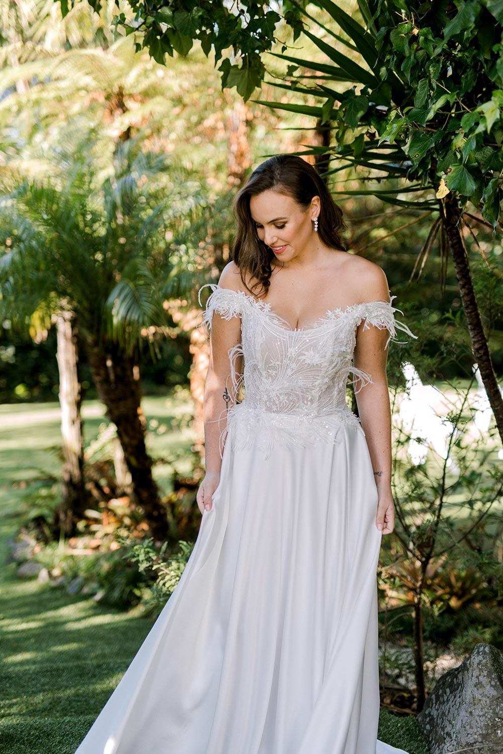 Genevive Wedding Dress from Vinka Design. The soft off-the-shoulder sleeves & semi-sheer structured bodice with hand-appliqued lace and a soft satin skirt make this a romantic & dreamy wedding dress. Side detail of dress with train, photographed at Tui Hills.