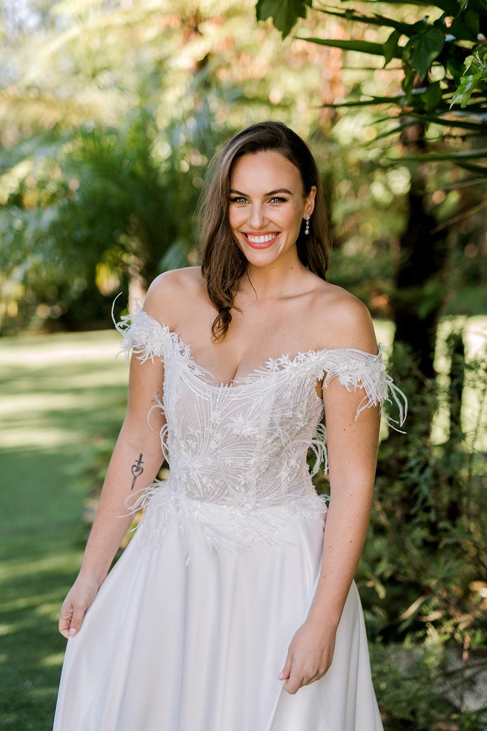 Genevive Wedding Dress from Vinka Design. The soft off-the-shoulder sleeves & semi-sheer structured bodice with hand-appliqued lace and a soft satin skirt make this a romantic & dreamy wedding dress. Top half detail of dress showing off the bodice, photographed at Tui Hills.