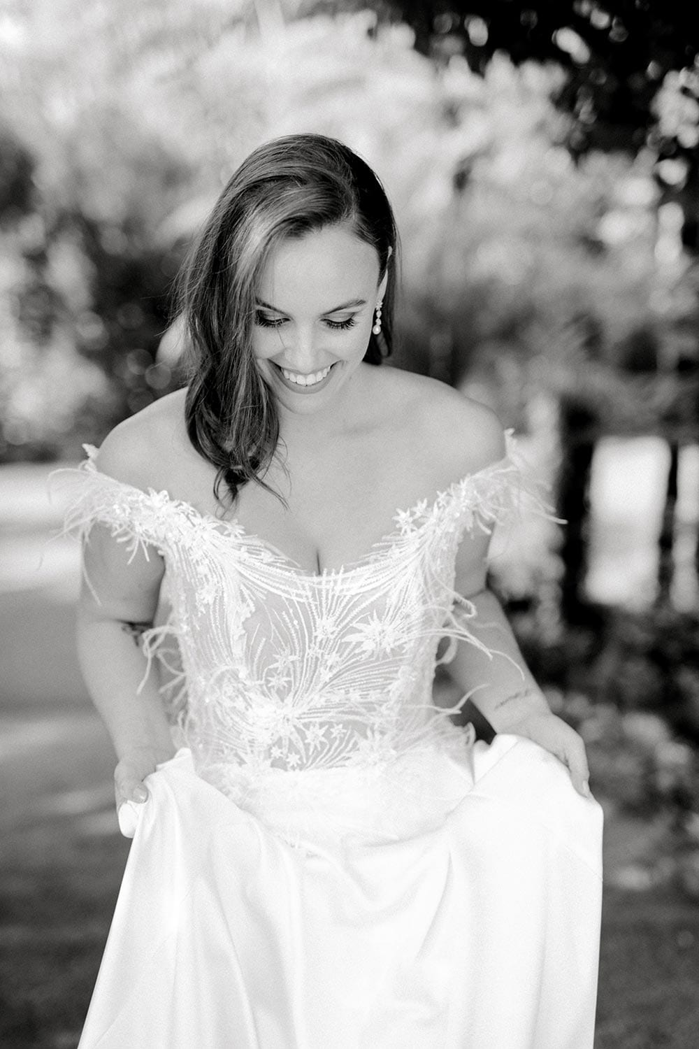 Genevive Wedding Dress from Vinka Design. The soft off-the-shoulder sleeves & semi-sheer structured bodice with hand-appliqued lace and a soft satin skirt make this a romantic & dreamy wedding dress. Top half detail of dress showing off the off-the-shoulder bodice in black and white, photographed at Tui Hills.