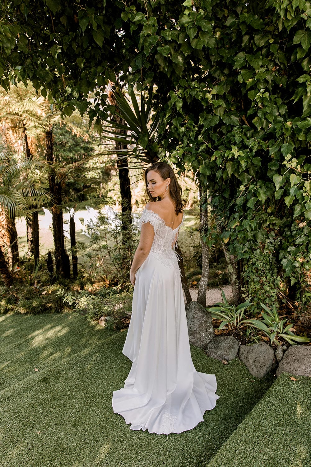 Genevive Wedding Dress from Vinka Design. The soft off-the-shoulder sleeves & semi-sheer structured bodice with hand-appliqued lace and a soft satin skirt make this a romantic & dreamy wedding dress. Back detail of dress with train, photographed at Tui Hills.