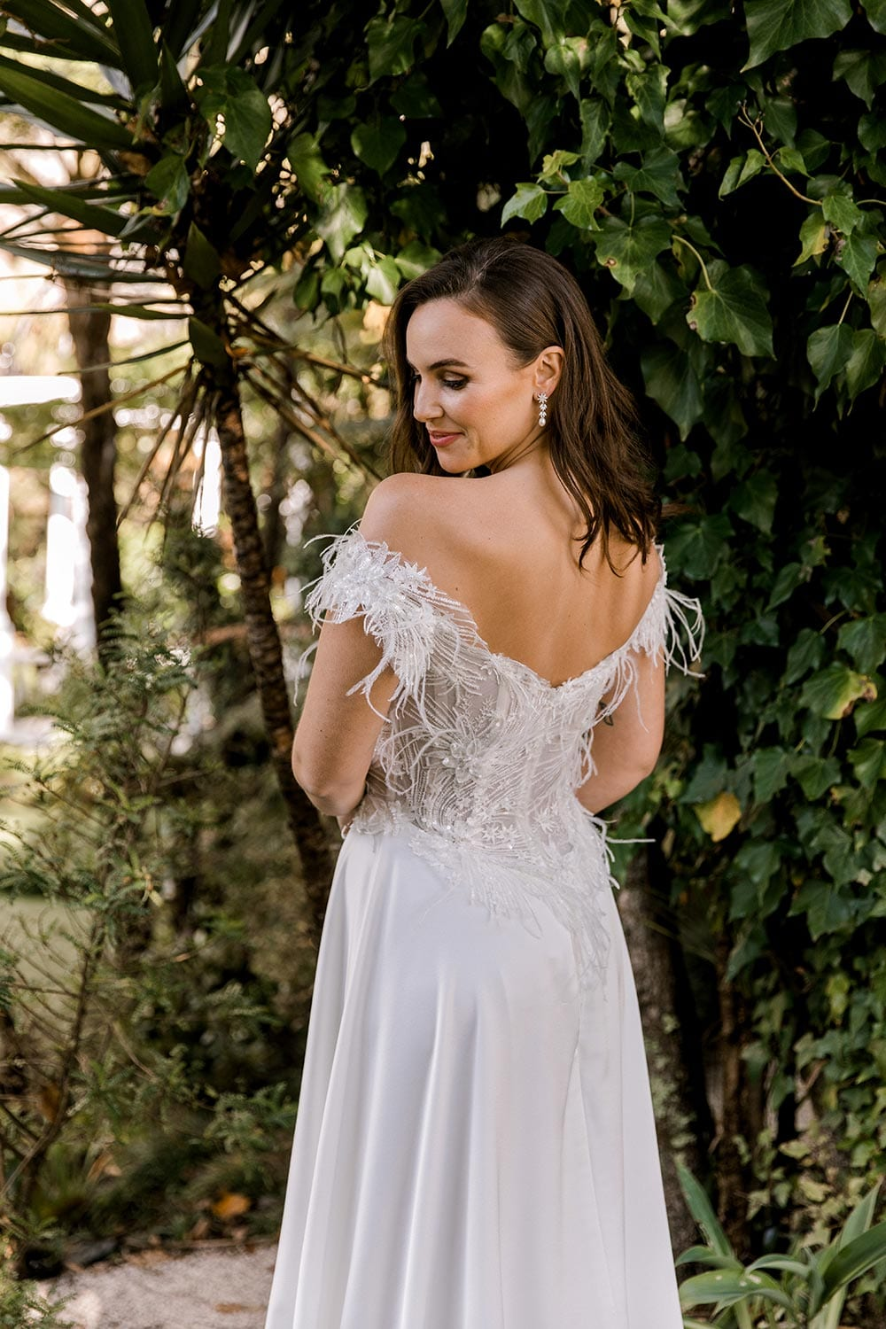 Genevive Wedding Dress from Vinka Design. The soft off-the-shoulder sleeves & semi-sheer structured bodice with hand-appliqued lace and a soft satin skirt make this a romantic & dreamy wedding dress. Close up detail of back detail of dress with train, photographed at Tui Hills.