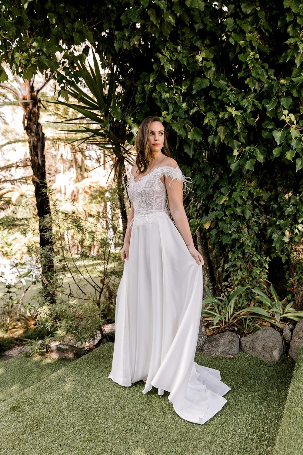 Genevive Wedding Dress from Vinka Design. The soft off-the-shoulder sleeves & semi-sheer structured bodice with hand-appliqued lace and a soft satin skirt make this a romantic & dreamy wedding dress. Full length portrait with train to the side, photographed at Tui Hills.