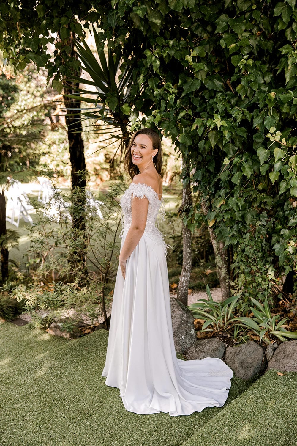 Genevive Wedding Dress from Vinka Design. The soft off-the-shoulder sleeves & semi-sheer structured bodice with hand-appliqued lace and a soft satin skirt make this a romantic & dreamy wedding dress. Full length portrait from the side with train, photographed at Tui Hills.