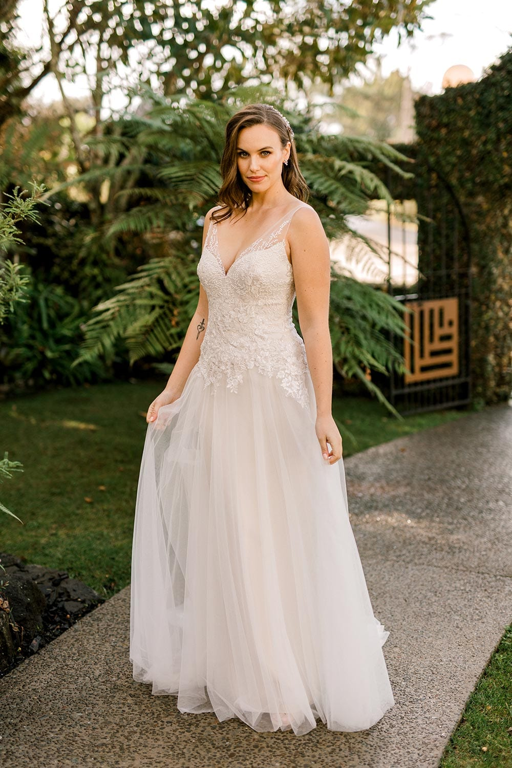 Hazel Wedding Dress from Vinka Design. Wedding dress with highly-sculptured bodice down to the hipline, at which point it gently flares into a beautiful and dreamy tulle skirt and train. Beautiful and delicate embroidery. Full length dress with skirt held.