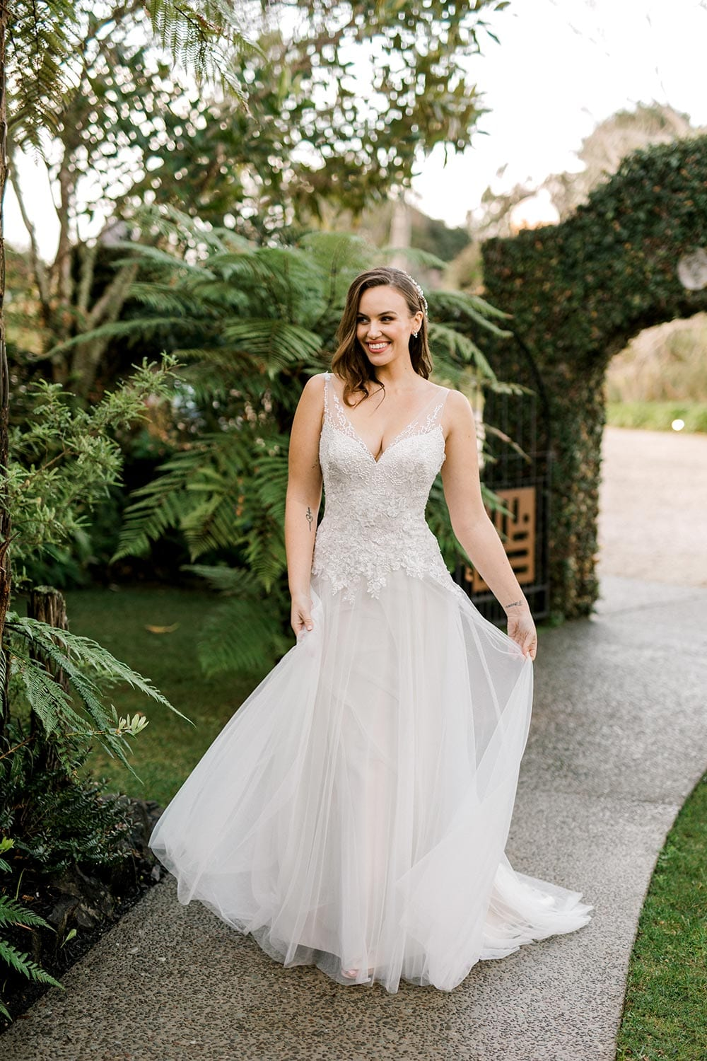 Hazel Wedding Dress from Vinka Design. Wedding dress with highly-sculptured bodice down to the hipline, at which point it gently flares into a beautiful and dreamy tulle skirt and train. Beautiful and delicate embroidery. Model walking with skirt flowing.