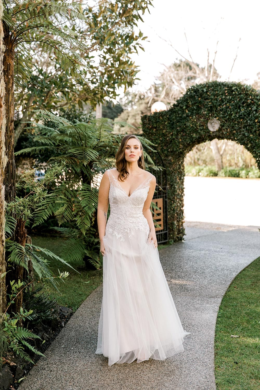 Hazel Wedding Dress from Vinka Design. Wedding dress with highly-sculptured bodice down to the hipline, at which point it gently flares into a beautiful and dreamy tulle skirt and train. Beautiful and delicate embroidery. Portrait with full dress length.