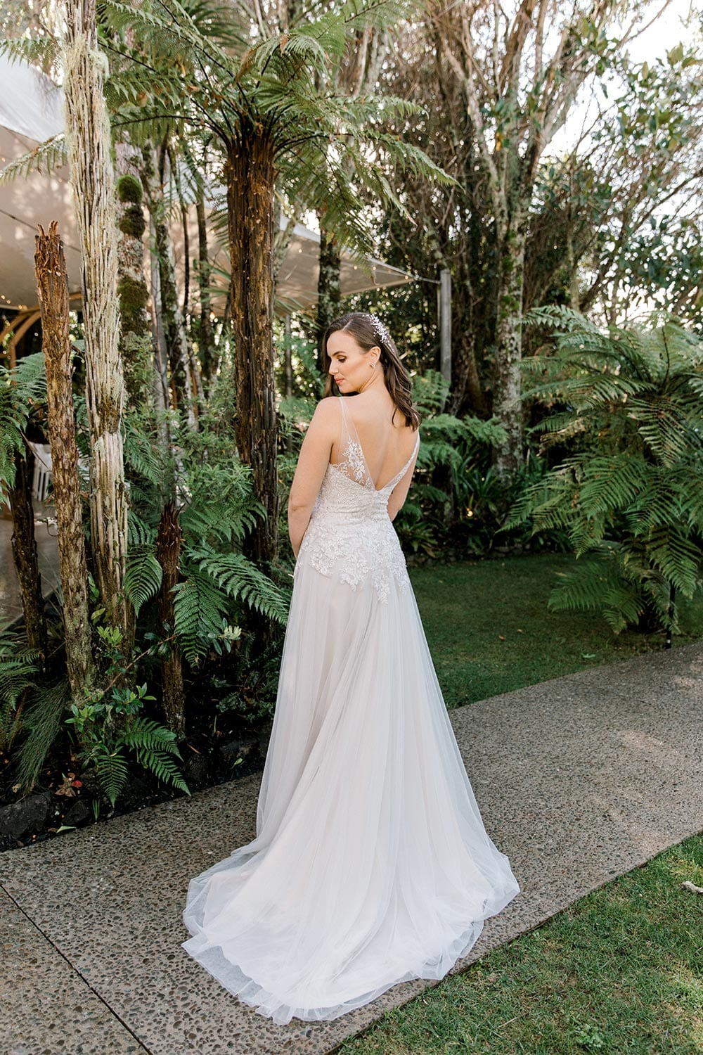Hazel Wedding Dress from Vinka Design. Wedding dress with highly-sculptured bodice down to the hipline, at which point it gently flares into a beautiful and dreamy tulle skirt and train. Beautiful and delicate embroidery. Model turning away full length dress detail.