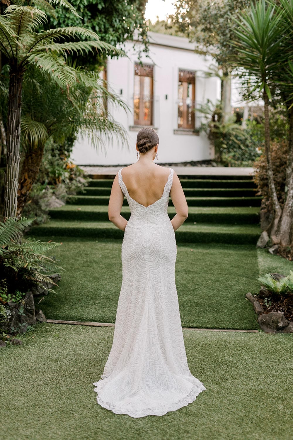 Juliette Wedding Dress from Vinka Design. Flattering stretch fitted lace wedding dress with beautiful ivory rich beading. Structured bodice provides support while remaining effortless to wear. Full length of dress from behind. Photographed at Tui Hills.