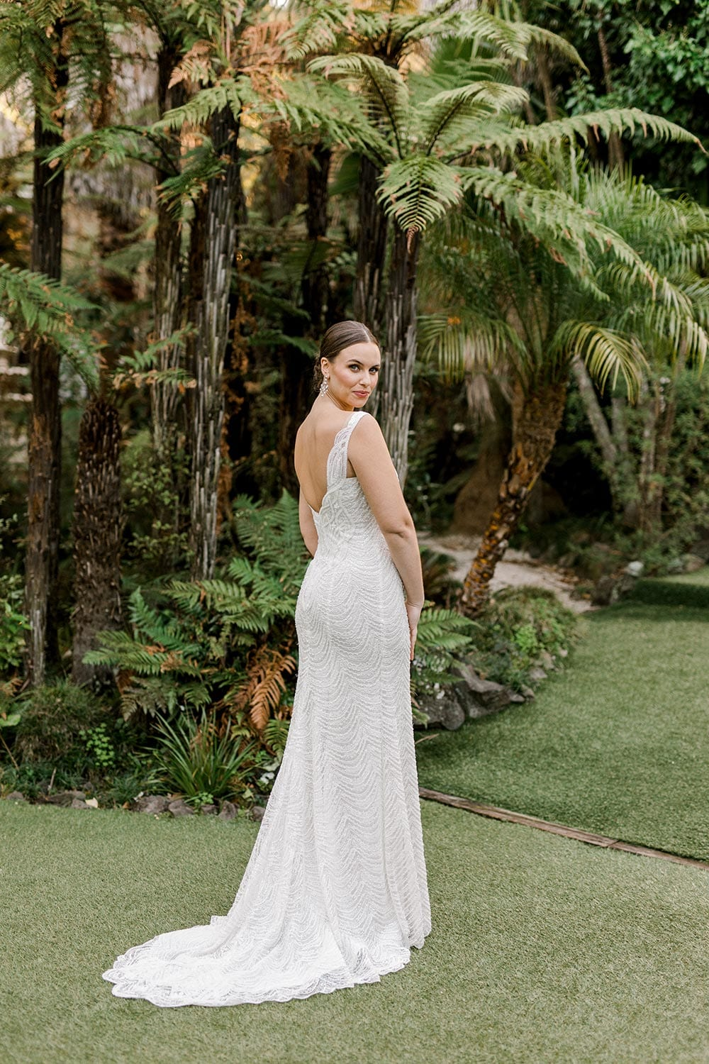 Juliette Wedding Dress from Vinka Design. Flattering stretch fitted lace wedding dress with beautiful ivory rich beading. Structured bodice provides support while remaining effortless to wear. Full length landscape of dress from behind with train flowing. Photographed at Tui Hills.