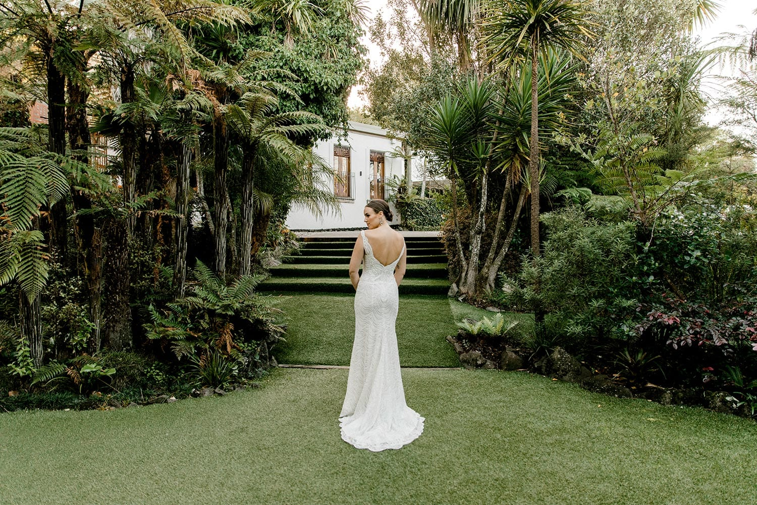 Juliette Wedding Dress from Vinka Design. Flattering stretch fitted lace wedding dress with beautiful ivory rich beading. Structured bodice provides support while remaining effortless to wear. Full length landscape of dress from behind with train to the side. Photographed at Tui Hills.