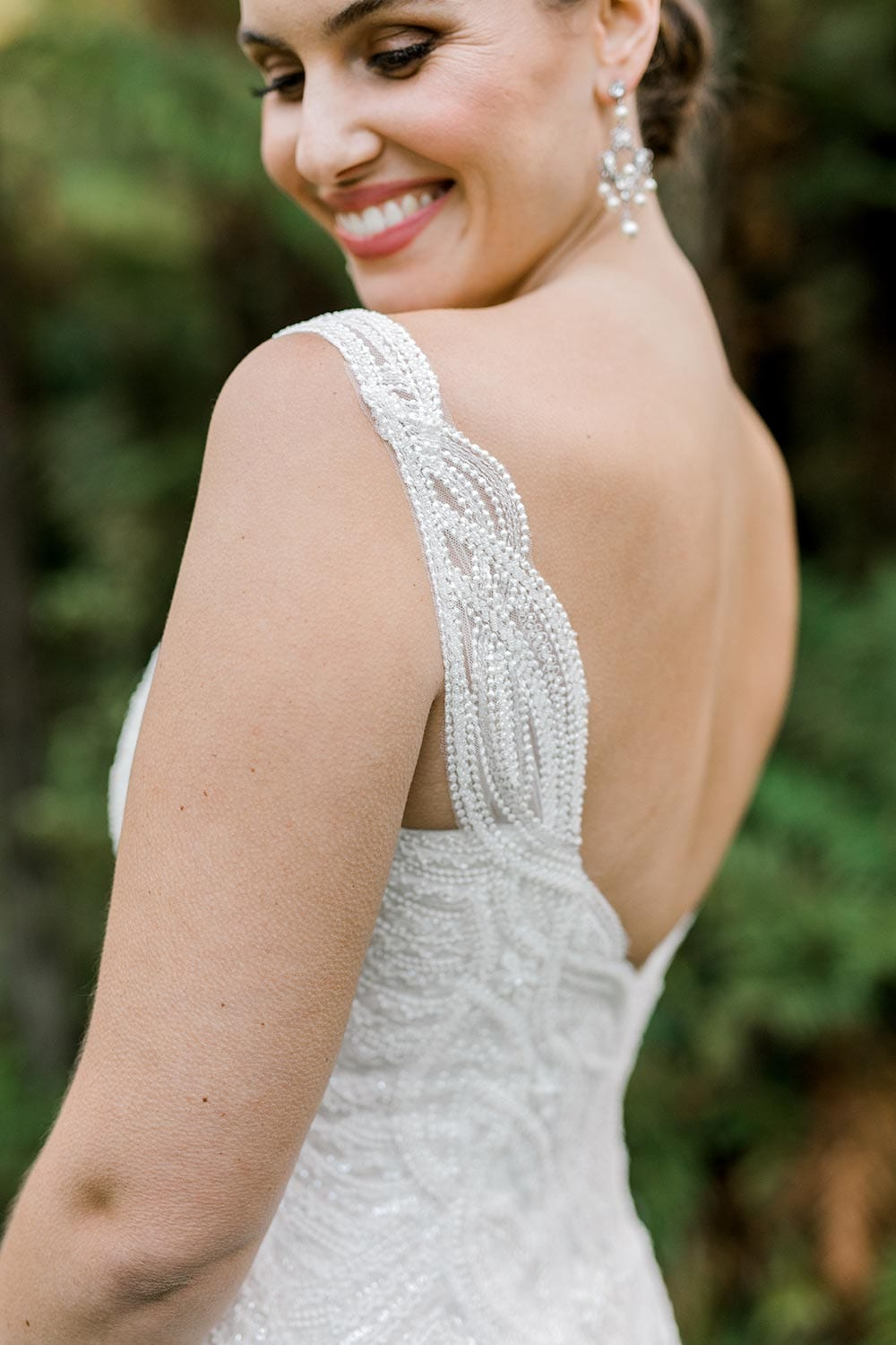Juliette Wedding Dress from Vinka Design. Flattering stretch fitted lace wedding dress with beautiful ivory rich beading. Structured bodice provides support while remaining effortless to wear. Close up detail of bodice with straps from the side. Photographed at Tui Hills.