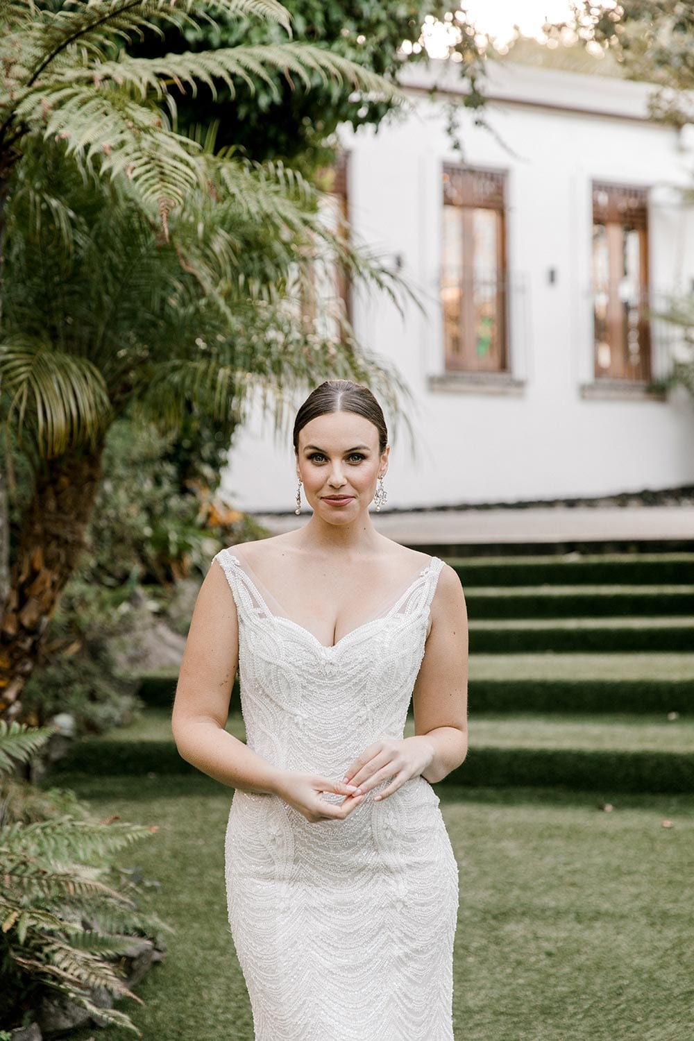 Juliette Wedding Dress from Vinka Design. Flattering stretch fitted lace wedding dress with beautiful ivory rich beading. Structured bodice provides support while remaining effortless to wear. Portrait with structured bodice with neckline. Photographed at Tui Hills.