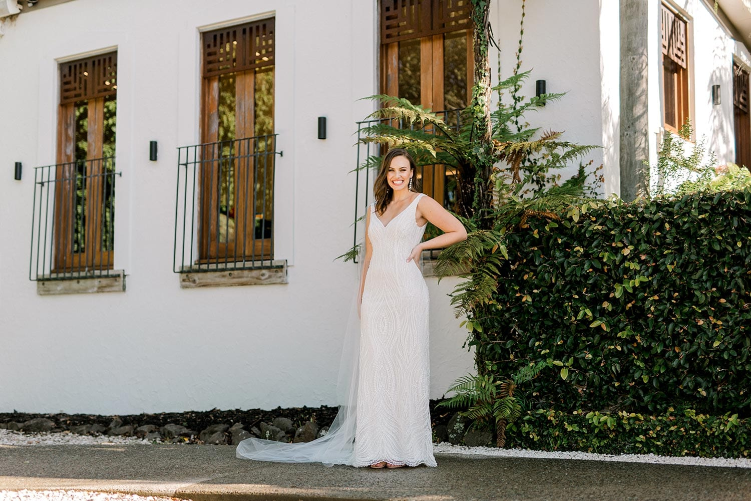 Kiera Wedding Dress from Vinka Design. Beautifully beaded lace wedding dress. Deep V-neckline both front and back is complemented with delicate sheer lace shoulder detail & structured bodice. Full length of dress with train to the side. Photographed at Tui Hills.