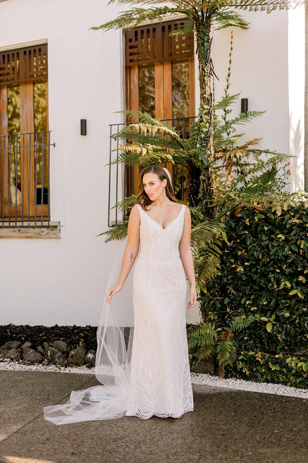 Kiera Wedding Dress from Vinka Design. Beautifully beaded lace wedding dress. Deep V-neckline both front and back is complemented with delicate sheer lace shoulder detail & structured bodice. Portrait showing full dress. Photographed at Tui Hills.