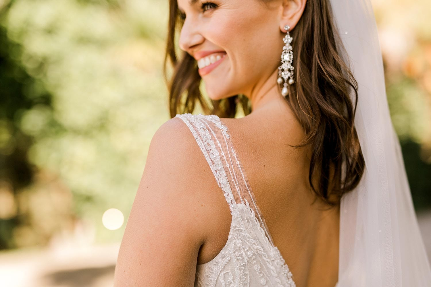 Kiera Wedding Dress from Vinka Design. Beautifully beaded lace wedding dress. Deep V-neckline both front and back is complemented with delicate sheer lace shoulder detail & structured bodice. Close up detail of shoulders. Photographed at Tui Hills.