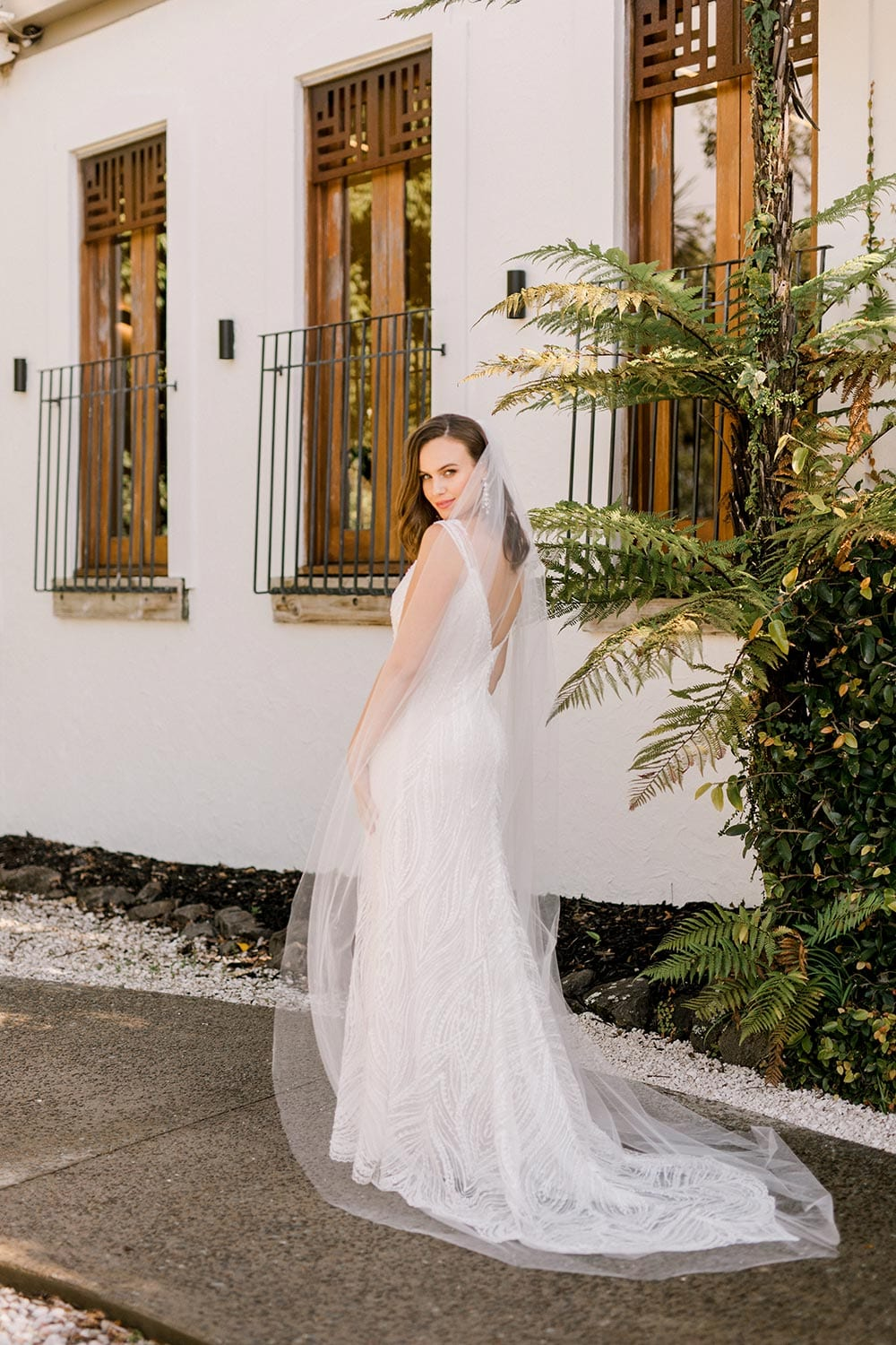 Kiera Wedding Dress from Vinka Design. Beautifully beaded lace wedding dress. Deep V-neckline both front and back is complemented with delicate sheer lace shoulder detail & structured bodice. Portrait showing full dress from the side. Photographed at Tui Hills.