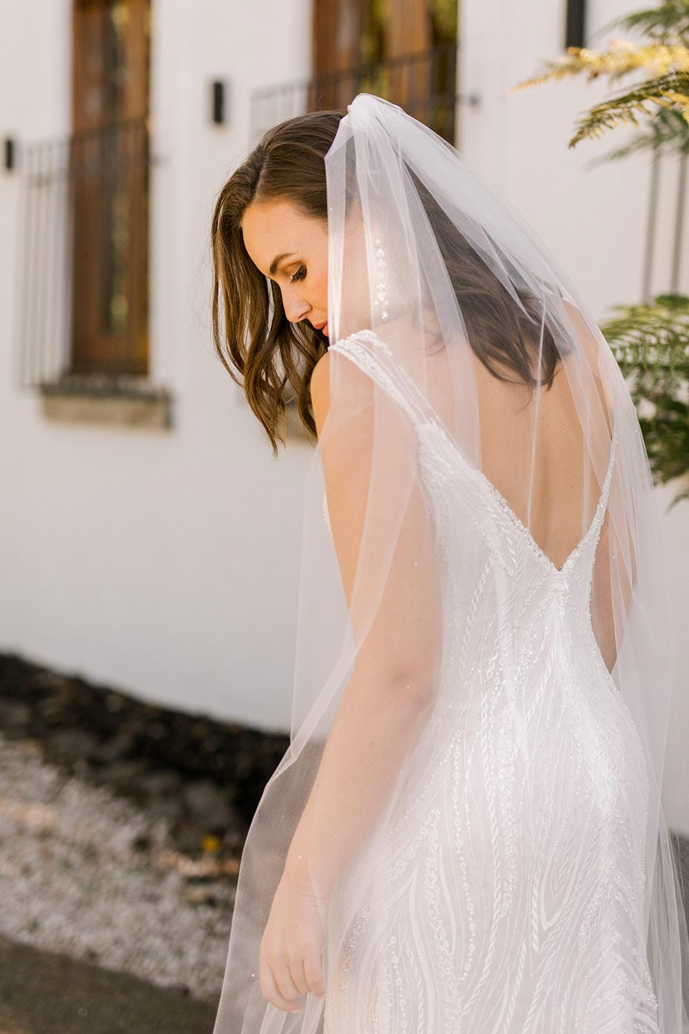 Kiera Wedding Dress from Vinka Design. Beautifully beaded lace wedding dress. Deep V-neckline both front and back is complemented with delicate sheer lace shoulder detail & structured bodice. Portrait showing top of dress from the back. Photographed at Tui Hills.