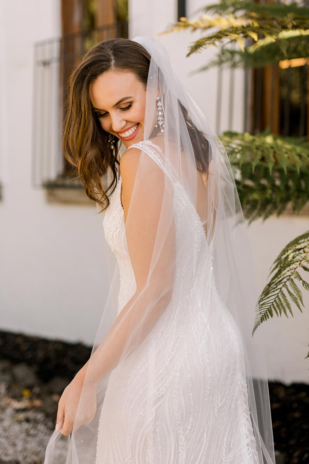 Kiera Wedding Dress from Vinka Design. Beautifully beaded lace wedding dress. Deep V-neckline both front and back is complemented with delicate sheer lace shoulder detail & structured bodice. Close up detail of dress from the side. Photographed at Tui Hills.