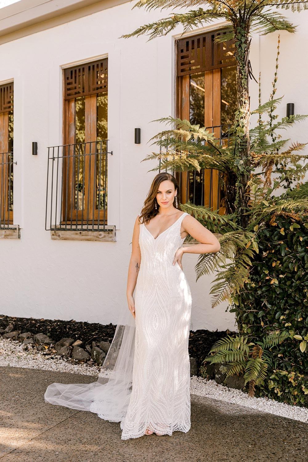 Kiera Wedding Dress from Vinka Design. Beautifully beaded lace wedding dress. Deep V-neckline both front and back is complemented with delicate sheer lace shoulder detail & structured bodice. Full length portrait of dress with train to side. Photographed at Tui Hills.