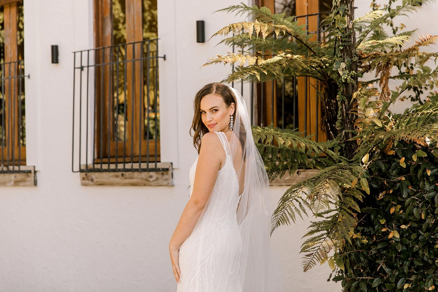Kiera Wedding Dress from Vinka Design. Beautifully beaded lace wedding dress. Deep V-neckline both front and back is complemented with delicate sheer lace shoulder detail & structured bodice. Close up detail of dress model looking back over shoulder. Photographed at Tui Hills.