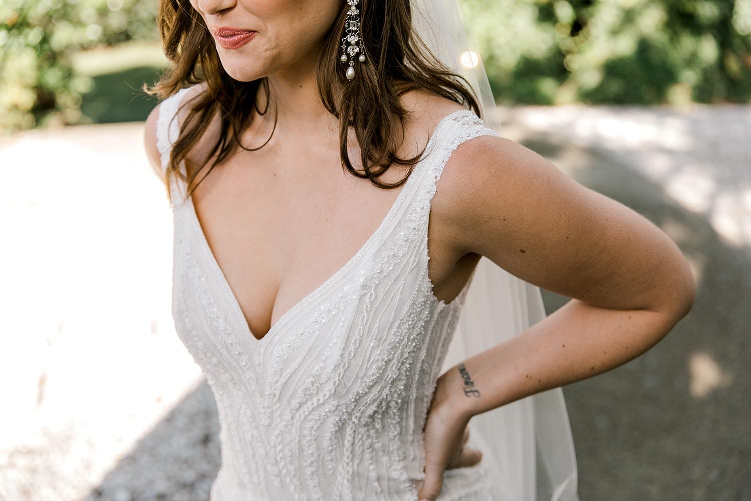 Kiera Wedding Dress from Vinka Design. Beautifully beaded lace wedding dress. Deep V-neckline both front and back is complemented with delicate sheer lace shoulder detail & structured bodice. Close up detail of structured bodice with low V-neckline. Photographed at Tui Hills.