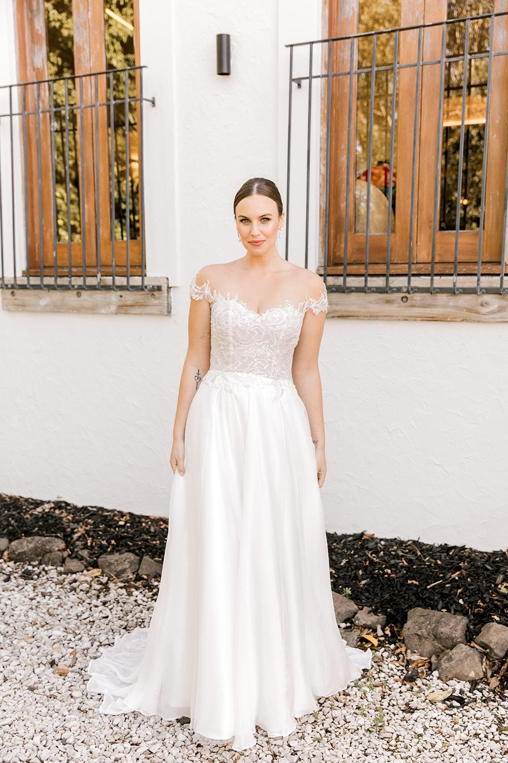 Lena Wedding Dress from Vinka Design. Gorgeous wedding dress with fitted bodice & dreamy silk chiffon & tulle skirt. Off-shoulder detail with an illusion neckline made with fine Italian tulle & lace detail. Full length front of dress. Photographed in front of beautiful old building.