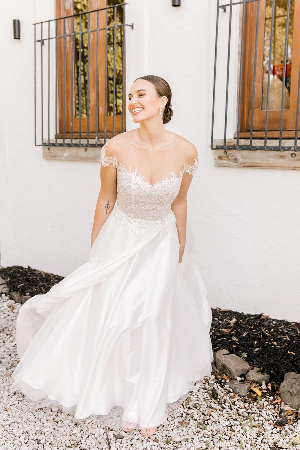 Lena Wedding Dress from Vinka Design. Gorgeous wedding dress with fitted bodice & dreamy silk chiffon & tulle skirt. Off-shoulder detail with an illusion neckline made with fine Italian tulle & lace detail. Full length with dress flowing. Photographed in front of beautiful old building.