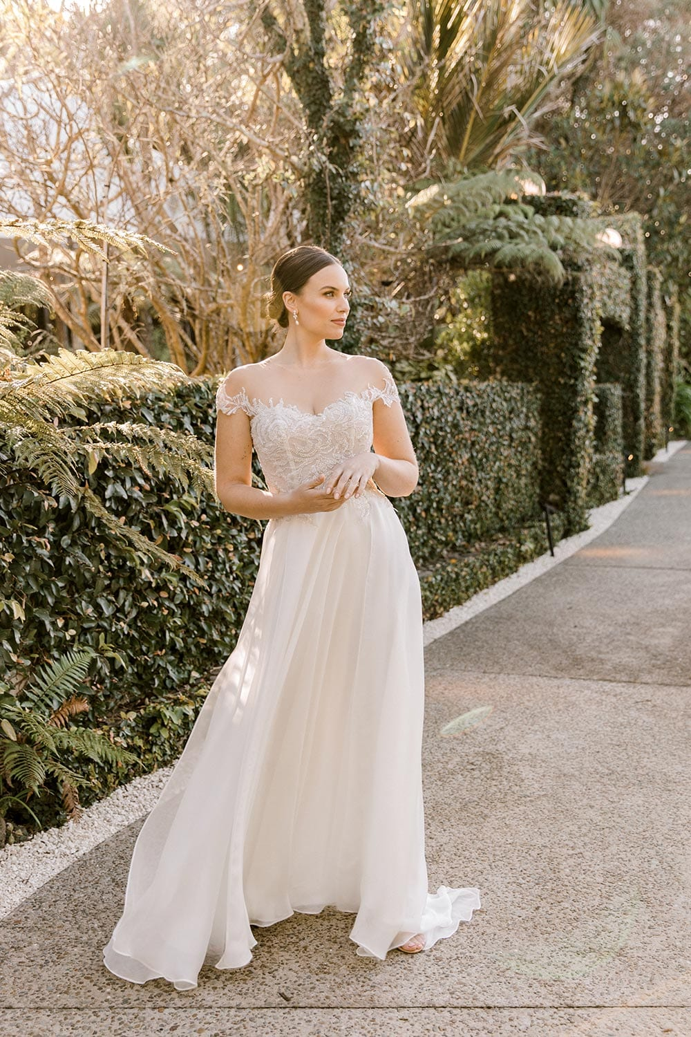 Lena Wedding Dress from Vinka Design. Gorgeous wedding dress with fitted bodice & dreamy silk chiffon & tulle skirt. Off-shoulder detail with an illusion neckline made with fine Italian tulle & lace detail. Full length portrait of dress. Photographed in front of beautiful old building.