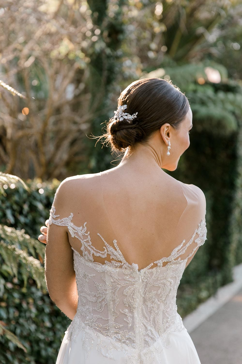 Lena Wedding Dress from Vinka Design. Gorgeous wedding dress with fitted bodice & dreamy silk chiffon & tulle skirt. Off-shoulder detail with an illusion neckline made with fine Italian tulle & lace detail. Detail of back of dress. Photographed in front of beautiful old building.