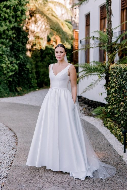 Madison Wedding Dress from Vinka Design Curve Collection. Classic Mikado satin wedding dress. Structured bodice with deep V-neckline & low back. Side pockets in the skirt give fun & versatility, with a sweeping train.