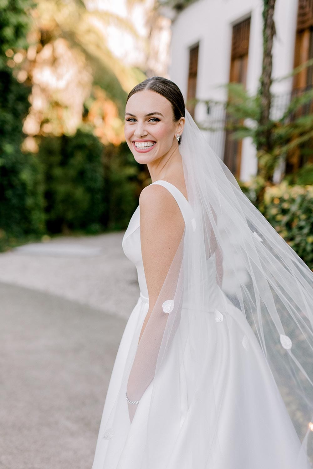 Madison Wedding Dress from Vinka Design. Classic Mikado satin wedding dress. Structured bodice with deep V-neckline & low back. Side pockets in the skirt give fun & versatility, with a sweeping train. View of gown from the side. Photographed outdoors.