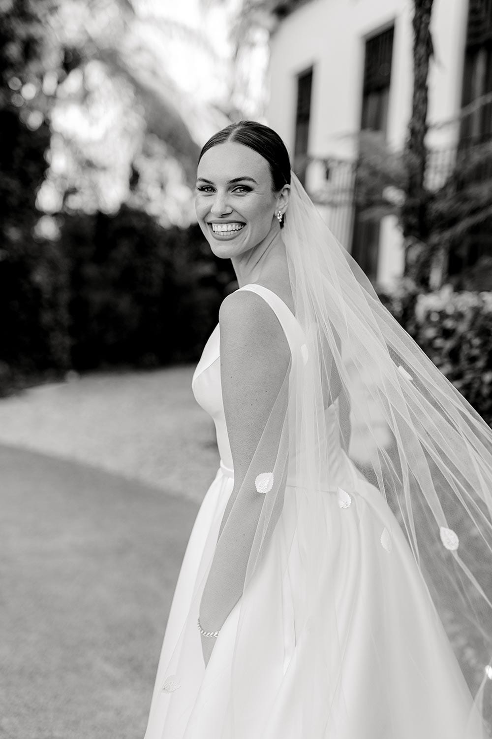 Madison Wedding Dress from Vinka Design. Classic Mikado satin wedding dress. Structured bodice with deep V-neckline & low back. Side pockets in the skirt give fun & versatility, with a sweeping train. View of gown from the side. Photographed outdoors. In Black & White.