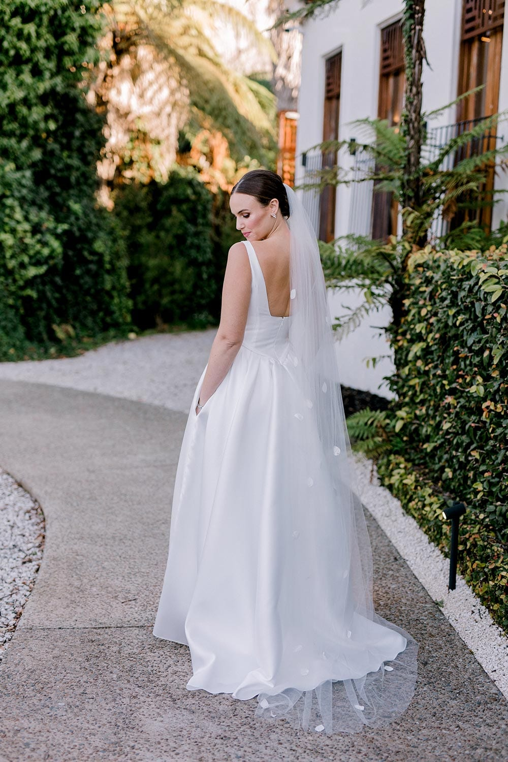Madison Wedding Dress from Vinka Design. Classic Mikado satin wedding dress. Structured bodice with deep V-neckline & low back. Side pockets in the skirt give fun & versatility, with a sweeping train. View of gown from the back. Photographed outdoors.