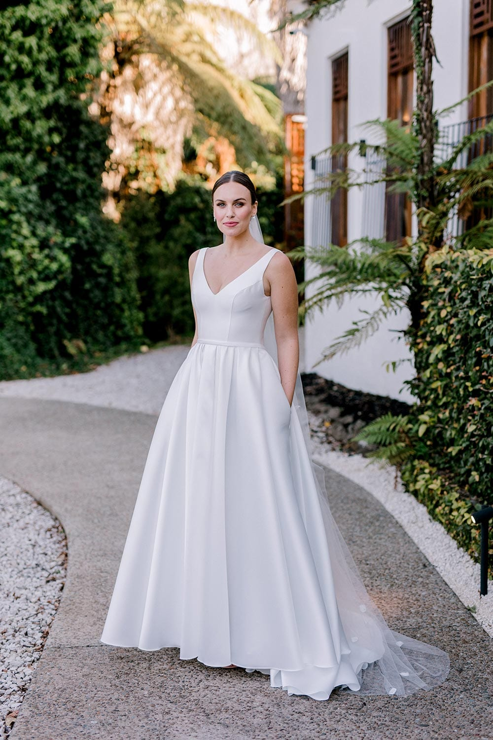 Madison Wedding Dress from Vinka Design. Classic Mikado satin wedding dress. Structured bodice with deep V-neckline & low back. Side pockets in the skirt give fun & versatility, with a sweeping train. Full length view of gown from the front, hands in pockets. Photographed outdoors.