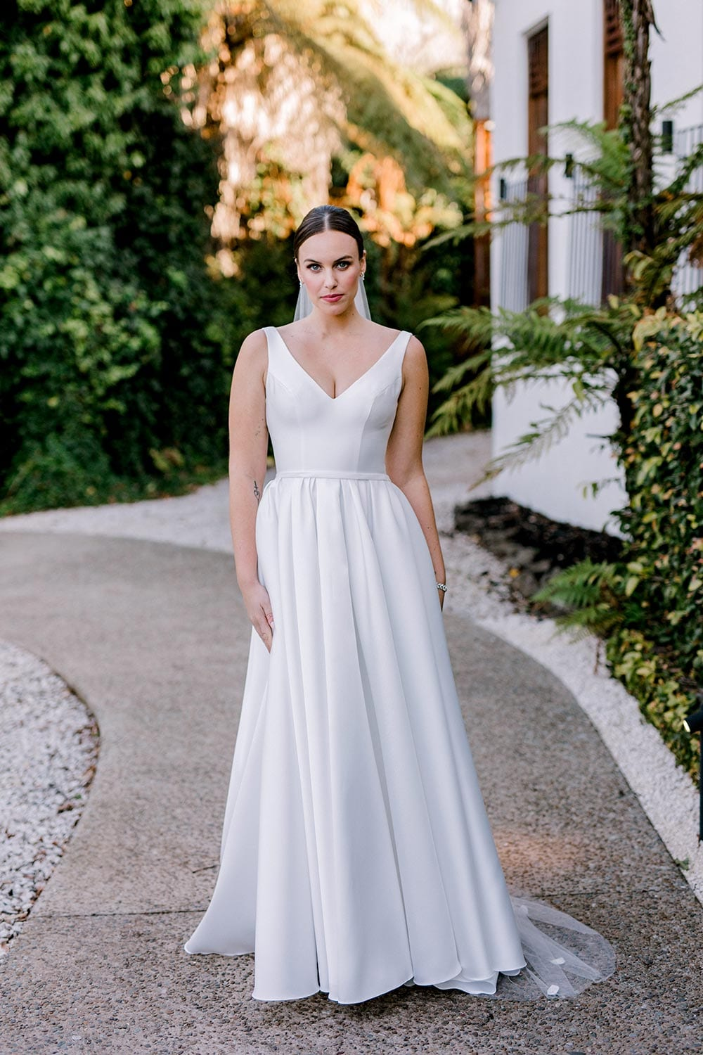 Madison Wedding Dress from Vinka Design. Classic Mikado satin wedding dress. Structured bodice with deep V-neckline & low back. Side pockets in the skirt give fun & versatility, with a sweeping train. Full length view of gown from the front. Photographed outdoors.