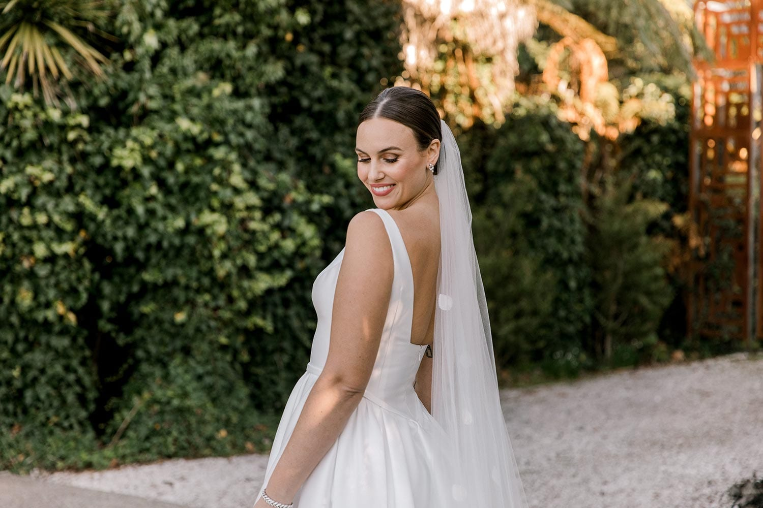 Madison Wedding Dress from Vinka Design. Classic Mikado satin wedding dress. Structured bodice with deep V-neckline & low back. Side pockets in the skirt give fun & versatility, with a sweeping train. View of bodice and back from the side. Photographed outdoors.