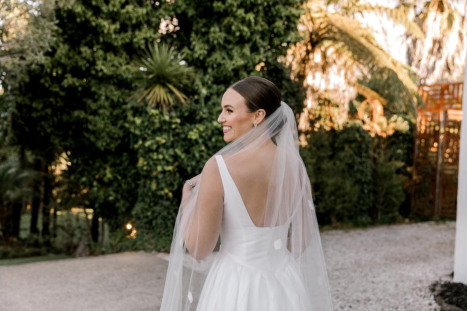 Madison Wedding Dress from Vinka Design. Classic Mikado satin wedding dress. Structured bodice with deep V-neckline & low back. Side pockets in the skirt give fun & versatility, with a sweeping train. Top half of gown from the back. Photographed outdoors.