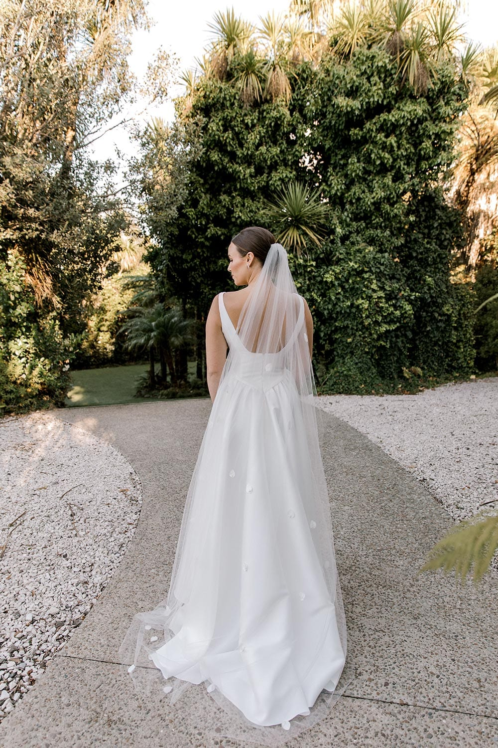 Madison Wedding Dress from Vinka Design. Classic Mikado satin wedding dress. Structured bodice with deep V-neckline & low back. Side pockets in the skirt give fun & versatility, with a sweeping train. Full length of gown from the back. Photographed outdoors.