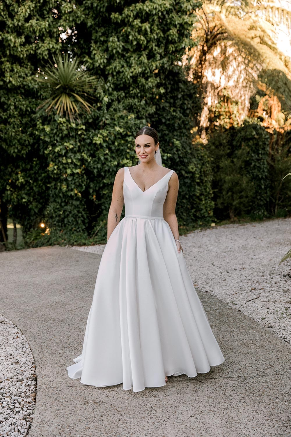 Madison Wedding Dress from Vinka Design. Classic Mikado satin wedding dress. Structured bodice with deep V-neckline & low back. Side pockets in the skirt give fun & versatility, with a sweeping train. Full length of gown from the front. Photographed outdoors.