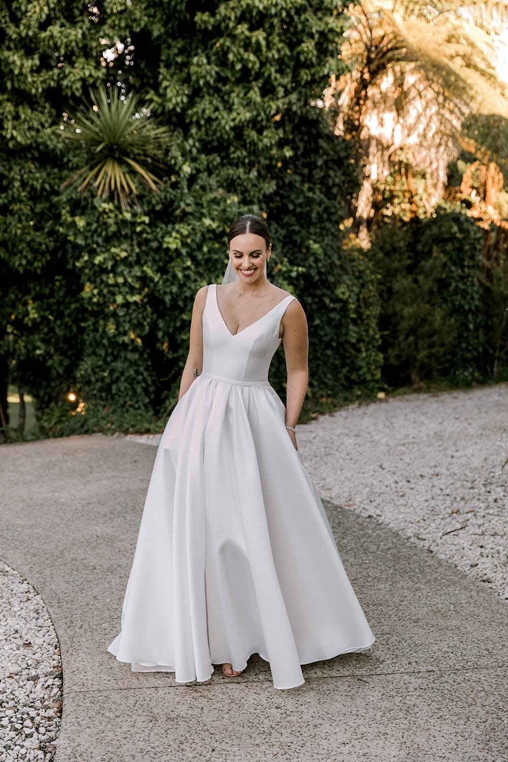 Madison Wedding Dress from Vinka Design. Classic Mikado satin wedding dress. Structured bodice with deep V-neckline & low back. Side pockets in the skirt give fun & versatility, with a sweeping train. Full length portrait with hands in pockets. Photographed outdoors.