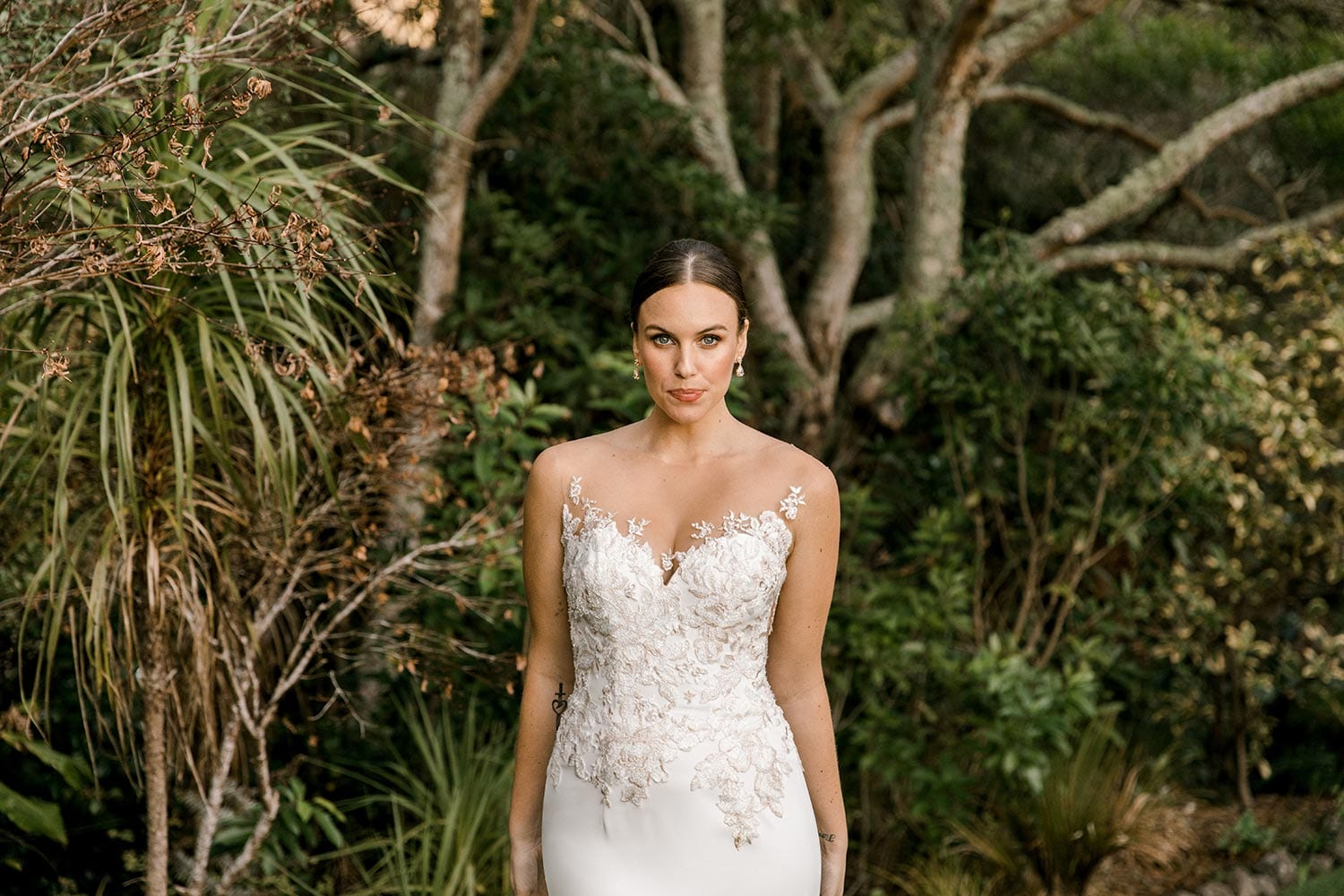 Samantha Wedding Dress from Vinka Design. This beautiful wedding dress has a nude sheer illusion strapless neckline made from fine Italian tulle. Low sheer back & structured bodice, & soft crepe train. Front detail of bodice. Photographed in Landscaped garden.