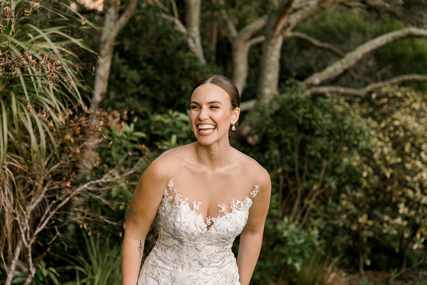 Samantha Wedding Dress from Vinka Design. This beautiful wedding dress has a nude sheer illusion strapless neckline made from fine Italian tulle. Low sheer back & structured bodice, & soft crepe train. Front detail of strapless illusion bodice. Photographed in Landscaped garden.