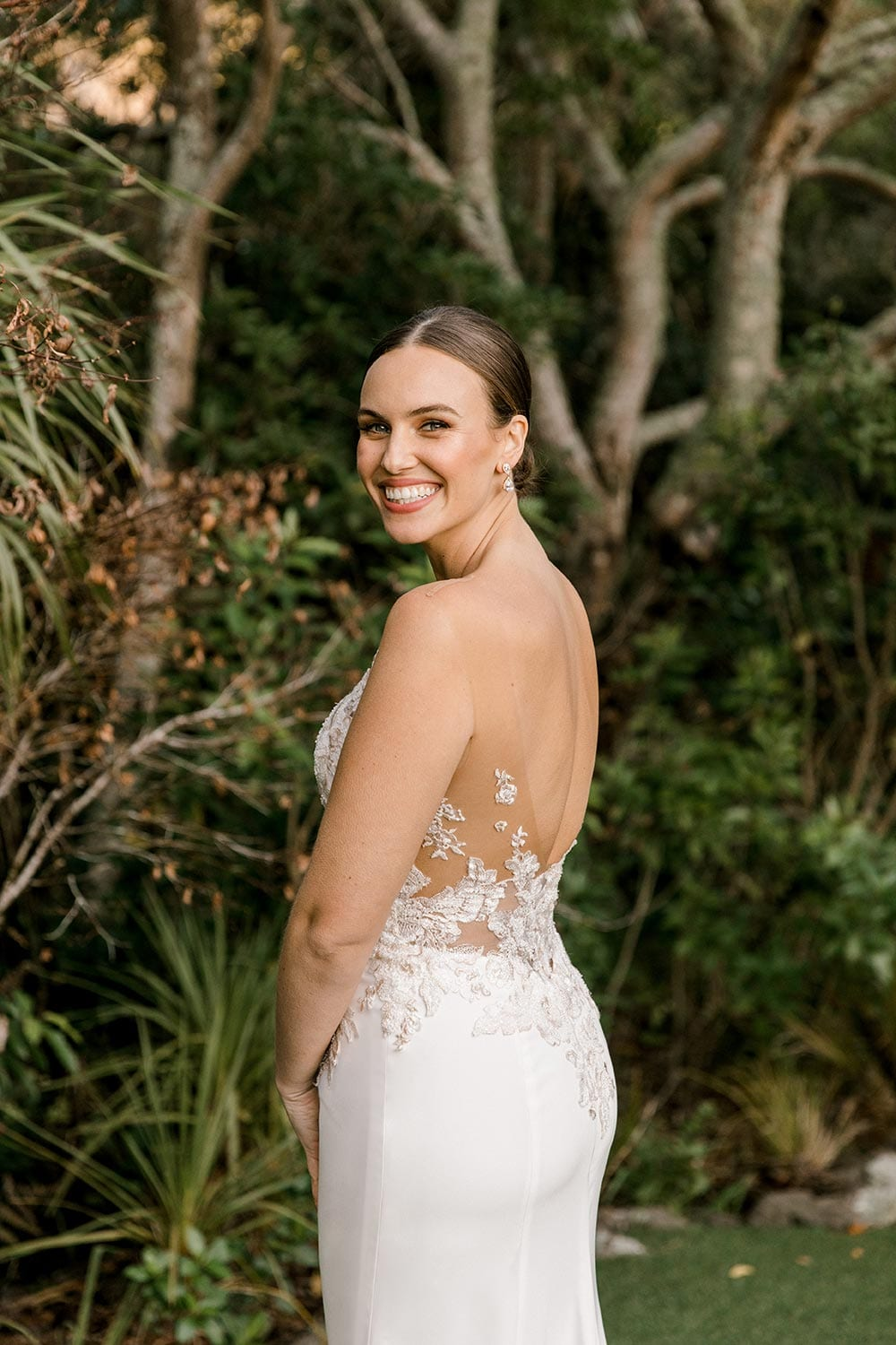 Samantha Wedding Dress from Vinka Design. This beautiful wedding dress has a nude sheer illusion strapless neckline made from fine Italian tulle. Low sheer back & structured bodice, & soft crepe train. Model looking over shoulder showing side of gown. Photographed in Landscaped garden.